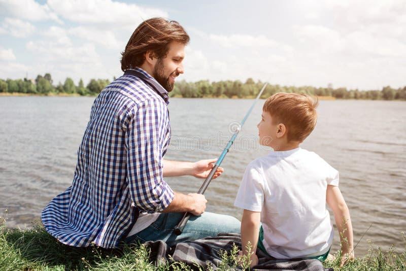 Vater und Sohn sitzen zusammen auf Gras und betrachten einander Kerl hält Fischstange in den Händen Er fischt lizenzfreie stockfotos