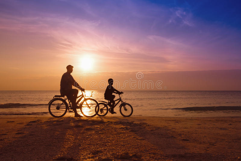 Vater und Sohn am Strand auf Sonnenuntergang lizenzfreie stockfotografie
