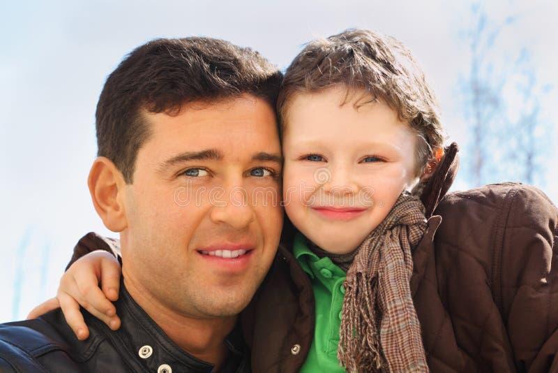 Vater und Sohn umarmen im Freien stockfotografie