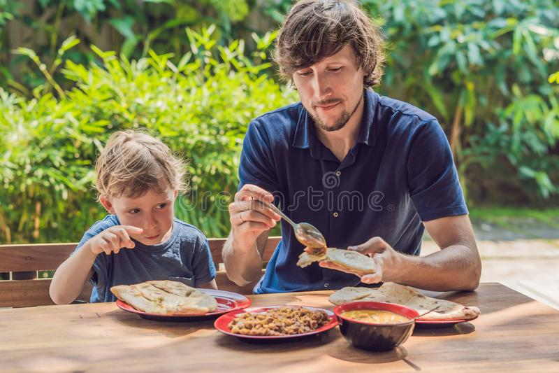 Vater und Sohn versuchen indisches Lebensmittel in einem Café auf der Straße lizenzfreie stockbilder