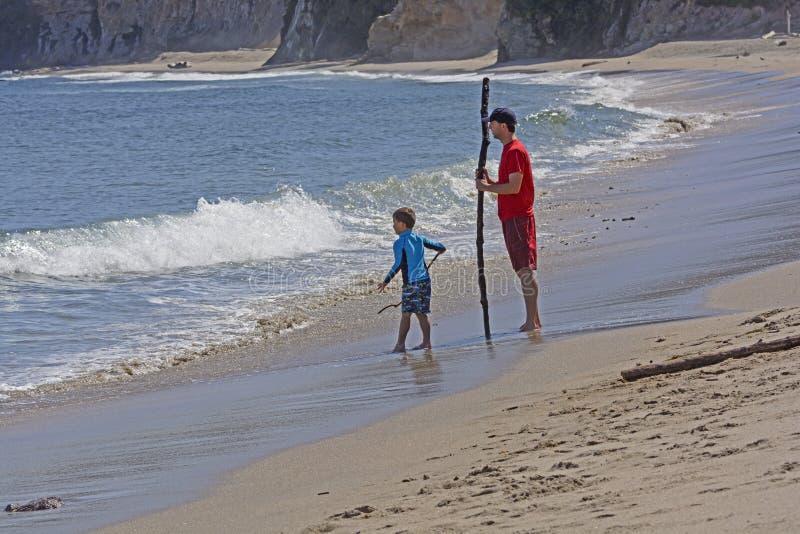 Vater und Sohn, welche die Wellen aufpassen lizenzfreie stockbilder