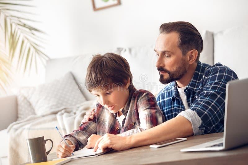 Vater und Sohn zu Hause, die bei Tisch Vativertretungsjungen sitzen, wie man Aufgabe tut stockbilder
