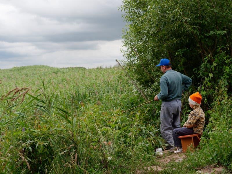 Vater- und Sohnfischen mit einer Angelrute lizenzfreie stockfotografie
