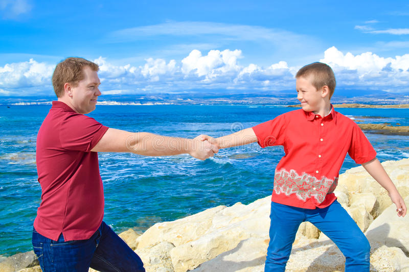 Vater- und Sohnhändchenhalten stockbilder