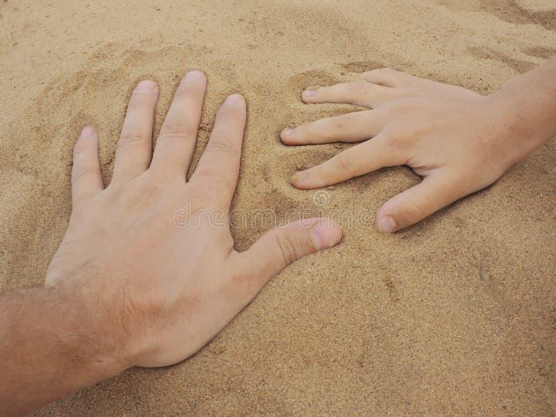 Vater- und Sohnhände auf Sand Abschluss oben stockfotografie