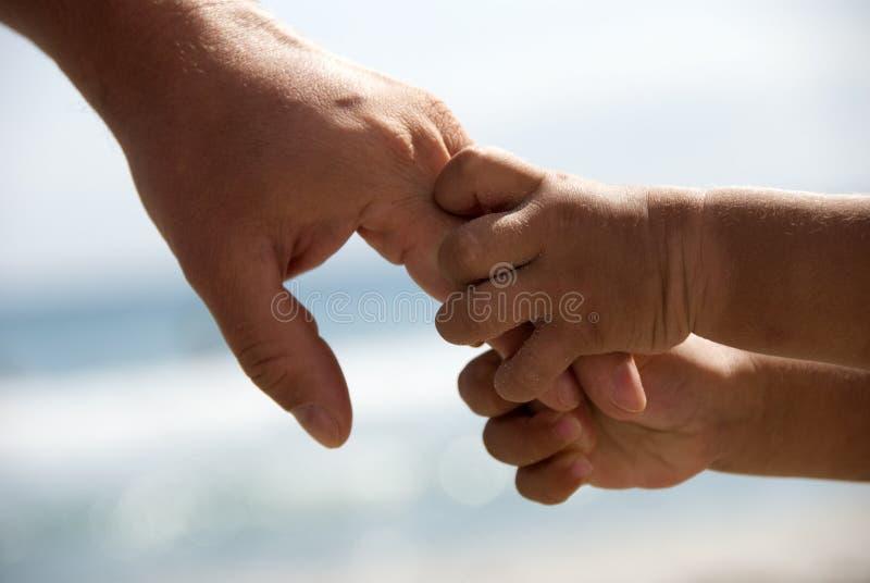 Vater- und Sohnholdinghände stockbild