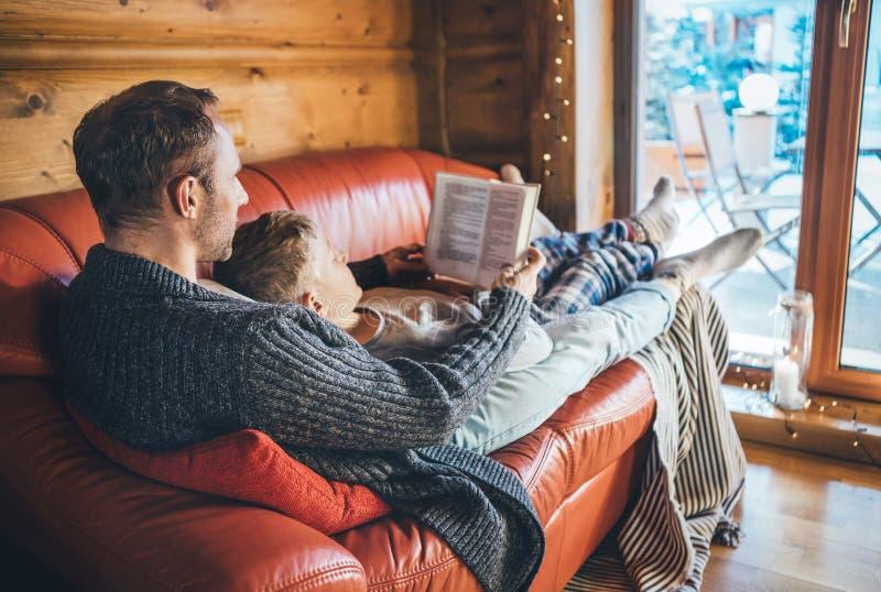 Vater- und Sohnlesebuch, das zusammen auf dem gemütlichen Sofa im warmen Landhaus liegt Lesung zum Kinderbegriffsbild stockfotografie