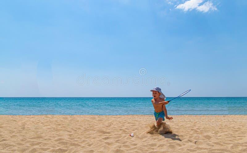 Vater- und Sohnspiel mit Federballschläger und Federball auf dem Strand stockbild