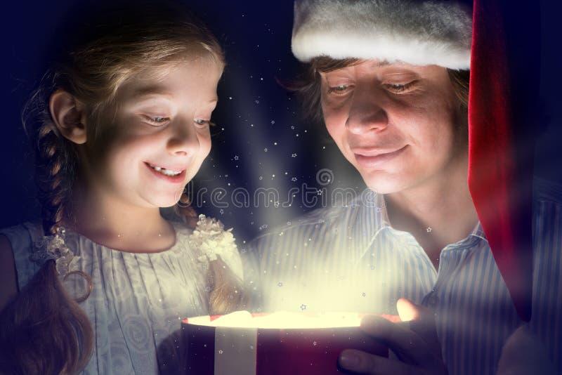 Vater und Tochter öffneten einen Kasten mit einem Geschenk stockbild