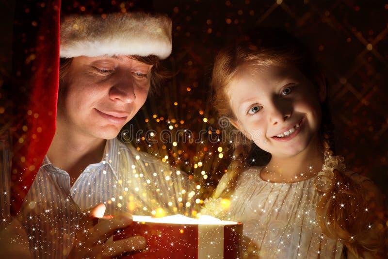 Vater und Tochter öffneten einen Kasten mit einem Geschenk stockbilder