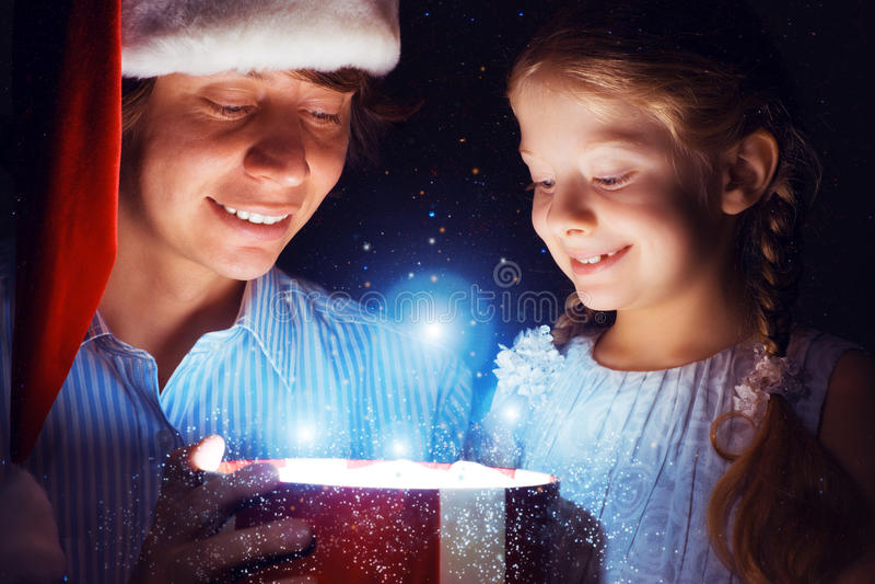 Vater und Tochter öffneten einen Kasten mit einem Geschenk lizenzfreies stockbild