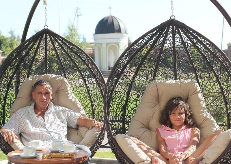 Vater und Tochter auf dem Sommerterrassencafé lizenzfreie stockfotos