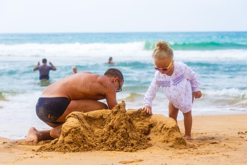 Vater und Tochter bauen Sandburg am Ufer eines tropischen Sandstrandes im Hintergrund der Badegäste lizenzfreies stockbild