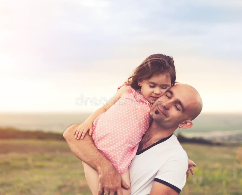 Vater und Tochter, die auf Sommersonnenuntergang umarmen stockbild