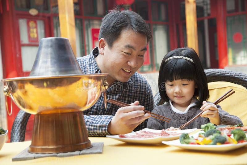 Vater und Tochter, die draußen chinesische Nahrung essen lizenzfreies stockfoto
