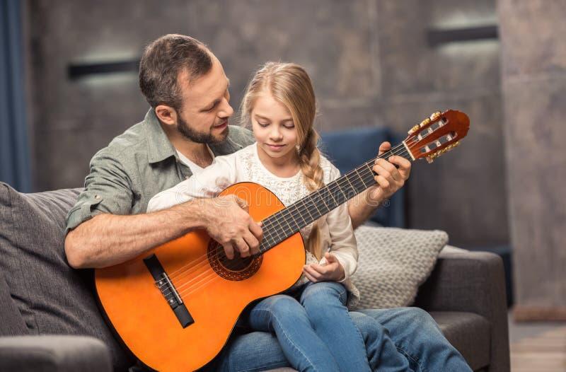Vater und Tochter, die Gitarre spielen lizenzfreie stockbilder