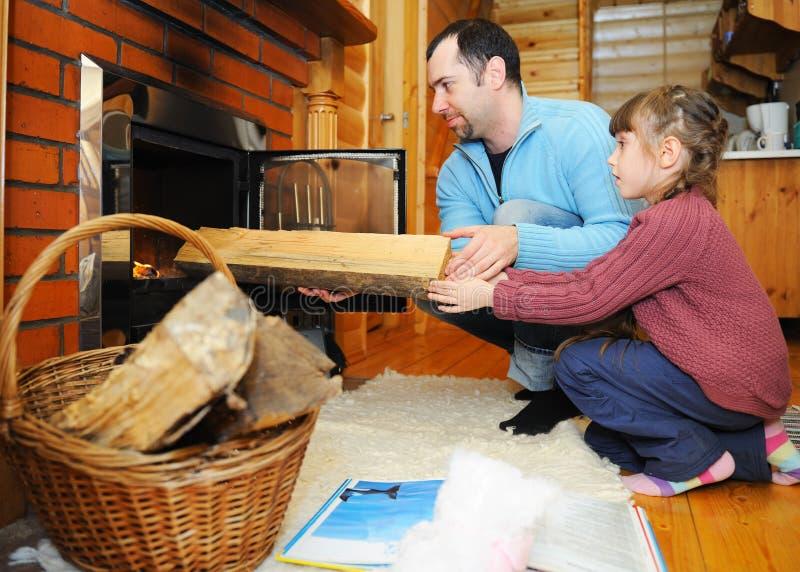 Vater und Tochter, die Holz in Kamin setzen stockfotos