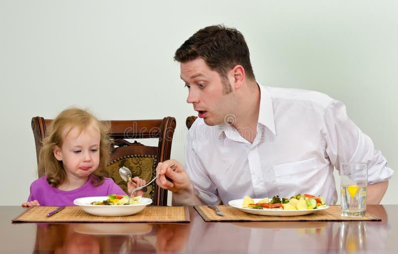 Vater und Tochter, die zu Abend essen stockbild