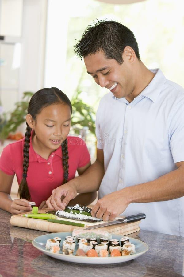 Vater und Tochter, die zusammen Sushi zubereiten lizenzfreie stockbilder