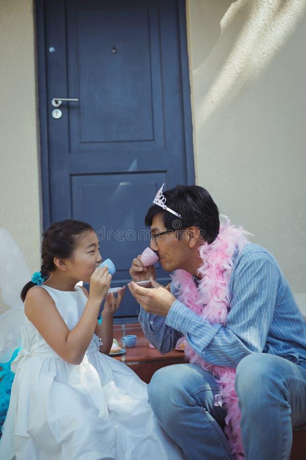 Vater und Tochter im feenhaften Kostüm, das eine Teeparty hat lizenzfreie stockfotos