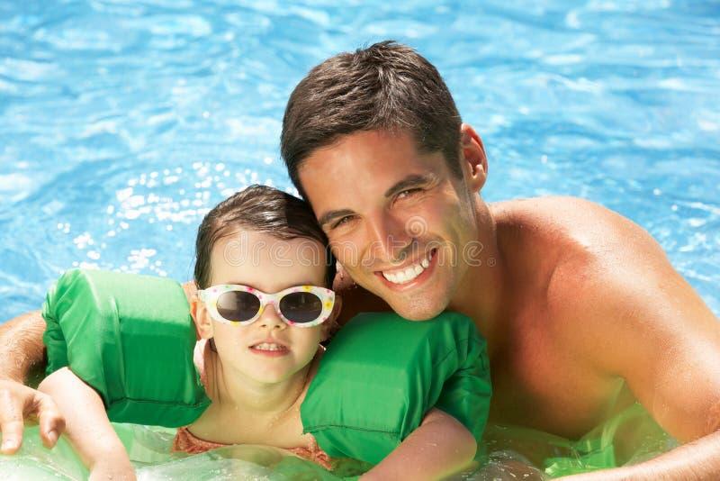 Vater und Tochter mit Armbinden im Swimmingpool lizenzfreies stockbild
