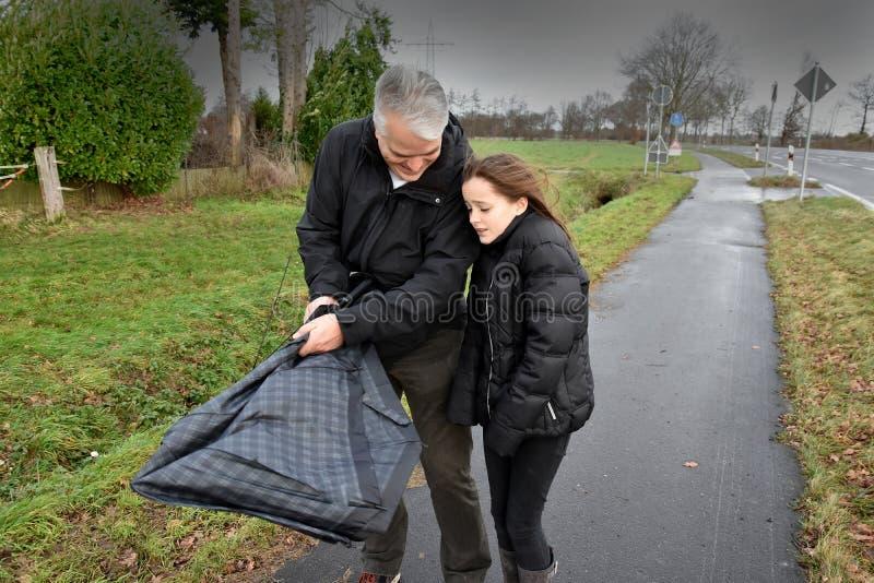 Vater und Tochter mit defektem Regenschirm lizenzfreies stockbild