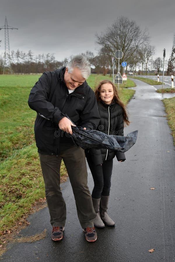 Vater und Tochter mit defektem Regenschirm stockfoto