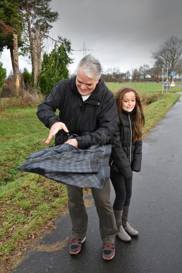 Vater und Tochter mit defektem Regenschirm lizenzfreie stockfotografie