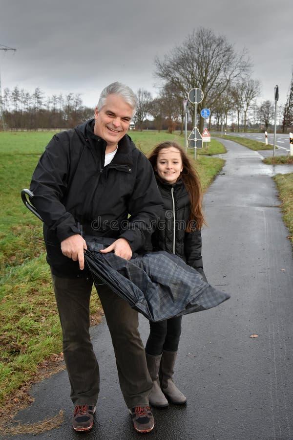 Vater und Tochter mit defektem Regenschirm lizenzfreies stockfoto