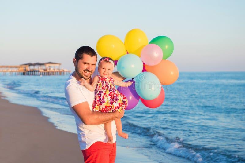 Vater und Tochter mit den Ballonen, die auf dem Strand zur Tageszeit spielen Konzept der freundlichen Familie stockfotografie