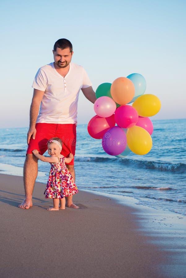 Vater und Tochter mit den Ballonen, die auf dem Strand zur Tageszeit spielen Konzept der freundlichen Familie stockfotos