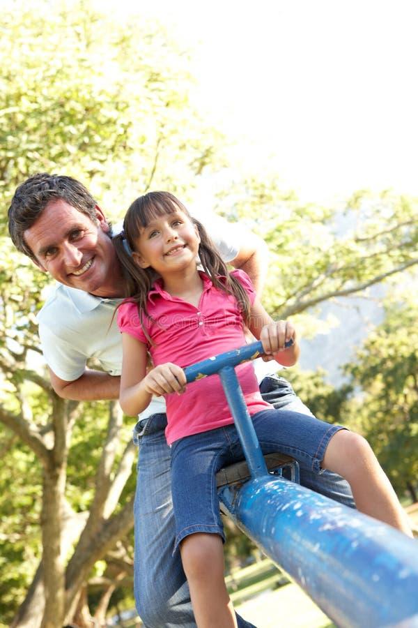 Vater-und Tochter-Reiten auf ständigem Schwanken in Playgroun stockbild