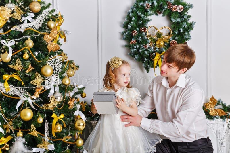 vater und tochter verzieren den weihnachtsbaum geschenke. Black Bedroom Furniture Sets. Home Design Ideas