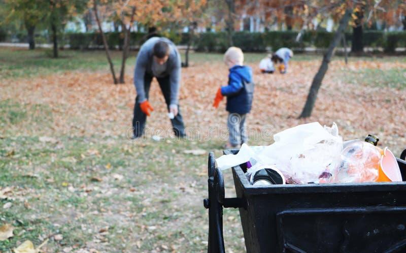 Vater und wenig Sohnausstossen von unreinheiten im Park Hintergrund - Abfall- und Sänftenbehälter Das Konzept von Ökologie und vo lizenzfreies stockbild