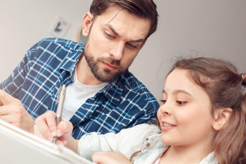Vater und wenig Tochter zu Hause, die bei Tisch das Mädchen tut Aufgabe während Vaterkümmern sitzt lizenzfreie stockfotos