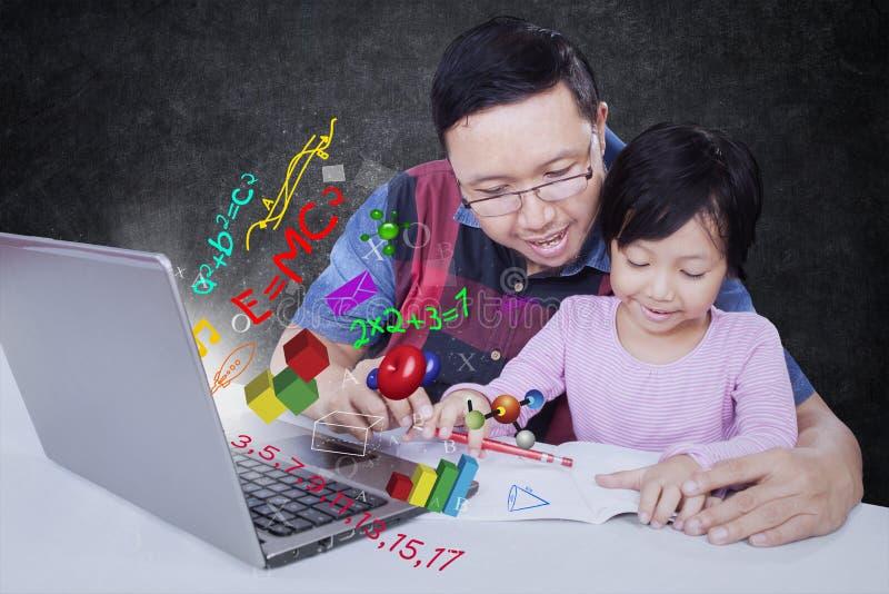 Vater, welche seiner Tochter hilft zu studieren stockbild