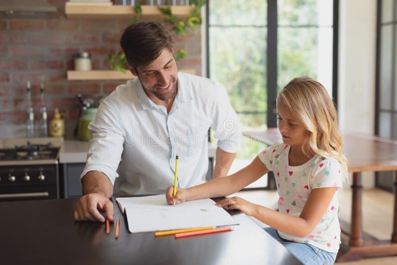 Vater, welche seiner Tochter mit Hausarbeit in einem behaglichen Haus hilft lizenzfreie stockbilder
