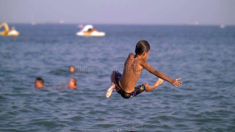 Vater wirft oben seinen Sohn in das Meer für einen Sprung, Junge in der Luft über dem Meer lizenzfreies stockfoto