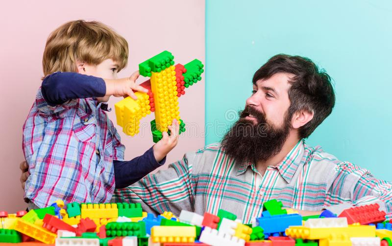 Vaterf?hrer-Vertretungsjunge, wie in erfolgreichen Mann wachsen Sie Vati und Kind Plastikbl?cke errichten Kinderbetreuung und Erz lizenzfreies stockfoto