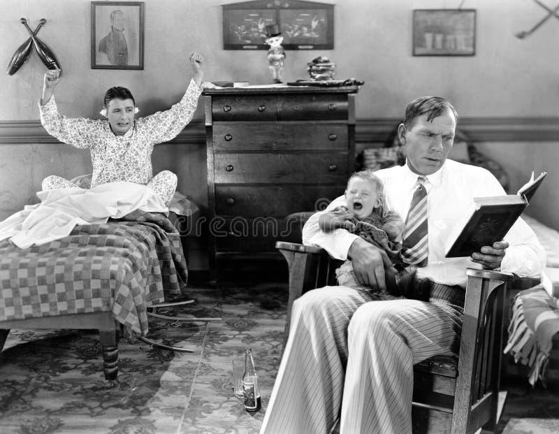 Vaterlesung mit einem schreienden Baby und einem Freund mit Baumwolle in seinen Ohren (alle dargestellten Personen sind nicht län stockbild