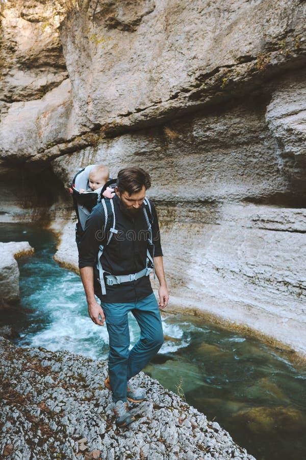 Vaterwanderung in Canyon mit Baby-Rucksack-Träger stockfotografie