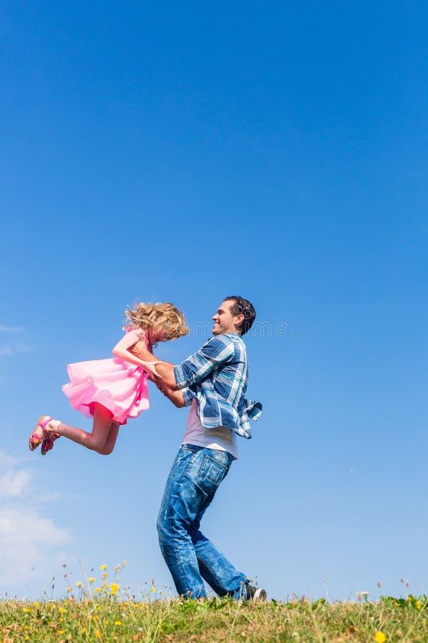 Vati, der herum seine Tochter spinnt lizenzfreies stockbild
