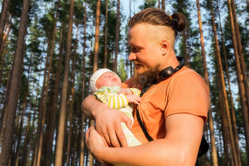 Vati, der leicht sein Baby in seinen Armen beim Trevelling im Holz h?lt lizenzfreie stockbilder