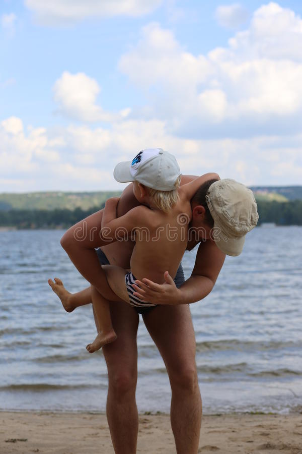 Vati, der mit jungem Sohn nahe dem Fluss spielt stockbild