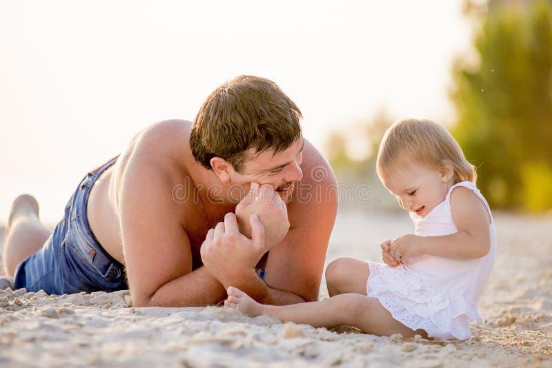 Vati, der mit seiner kleinen Tochter auf dem Strand spielt stockfoto