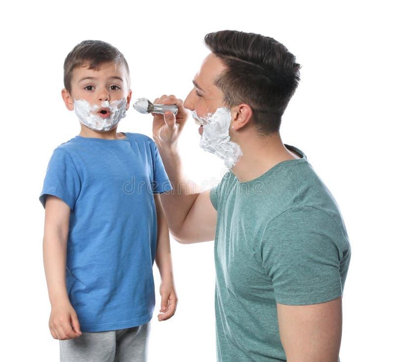 Vati, der Schaum auf das Gesicht des Sohns rasierend zutrifft stockfotografie