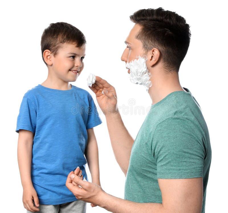 Vati, der Schaum auf das Gesicht des Sohns rasierend zutrifft lizenzfreie stockbilder