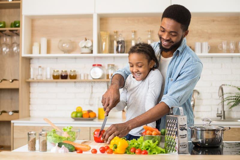 Vati, der seine Tochter unterrichtet, Salat zu kochen stockbild