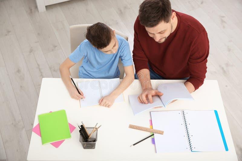Vati, der seinem Sohn mit Hausarbeit im Raum hilft lizenzfreie stockfotos