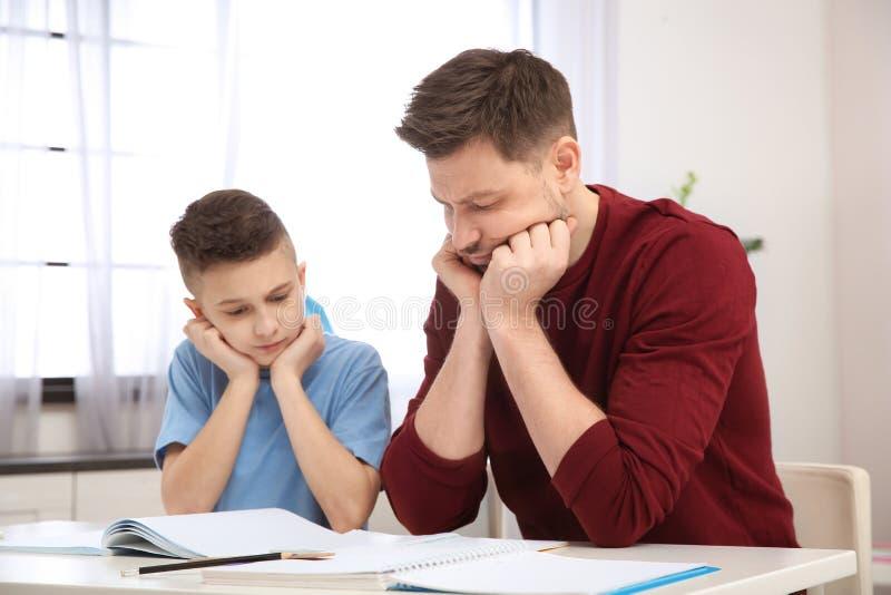 Vati, der seinem Sohn mit schwieriger Hausaufgabe hilft lizenzfreie stockfotografie